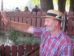 Sakis winkt seinen Gästen, die auf seinem Stocherkahn in Tübingen warten, von der Neckarmüller Anlegestelle zu
